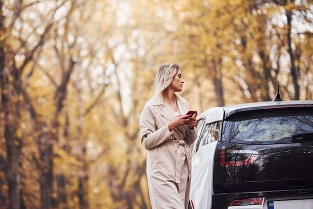 Usando smartphone. menina tem viagem de outono de carro. automóvel novo moderno na floresta.