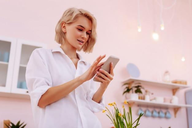 Usando smartphone. mulher atraente com cabelo curto em pé na cozinha e usando smartphone