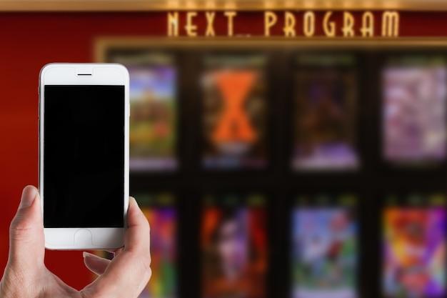 Usando smartphone reserva ingresso digital em aplicativo móvel no cinema e verificando programa de cinema conceito rápido e fácil