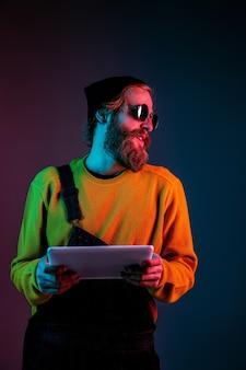 Usando tablet, parece feliz. retrato do homem caucasiano em fundo gradiente de estúdio em luz de néon. lindo modelo masculino com estilo hippie. conceito de emoções humanas, expressão facial, vendas, anúncio.