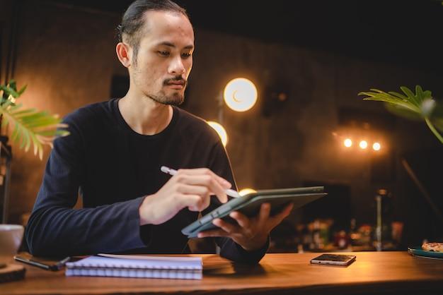 Usando tecnologia de tablet digital profissional para escrever um trabalho de negócios, comunicação on-line moderna no ciberespaço, escrita à mão com caneta branca, estilo de vida mesmo laptop ou notebook usando