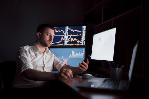 Usando tecnologias modernas no trabalho. jovem empresário trabalhando em tablet digital enquanto está sentado na mesa do escritório criativo