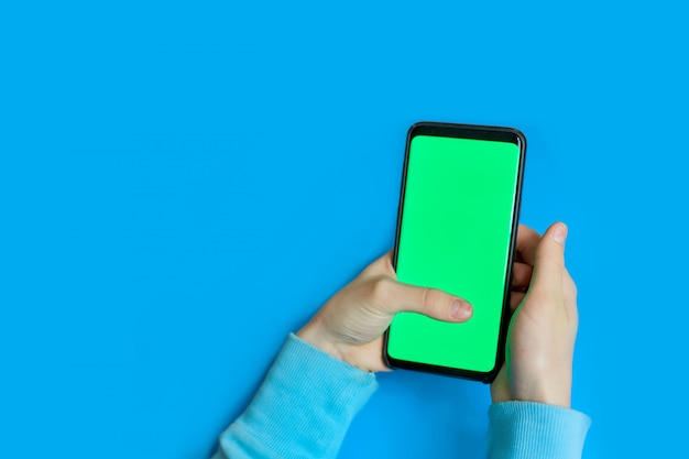 Usando telefone inteligente com tela verde. mãos rolando as páginas, tocando na tela de toque. vista do topo. chroma key