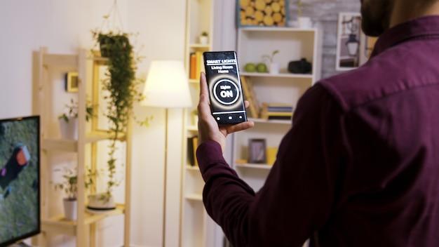Usando um aplicativo de luz inteligente para ligar as lâmpadas da casa. feche a filmagem em câmera lenta