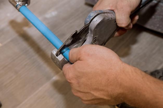 Usando um cortador para tubos de plástico, reparando os canos de água domésticos