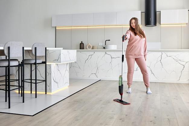 Usando um esfregão plano com spray e almofada de microfibra enquanto limpa a cozinha, uma jovem vestida de rosa escuta música e dança.