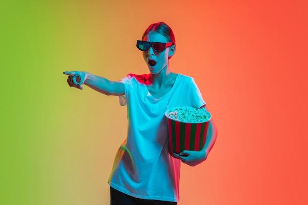Usando um fone de ouvido 3d, apontando com pipoca. retrato de jovem caucasiana em fundo gradiente estúdio verde-laranja em luz de néon. conceito de juventude, emoções humanas, expressão facial, vendas, anúncio.
