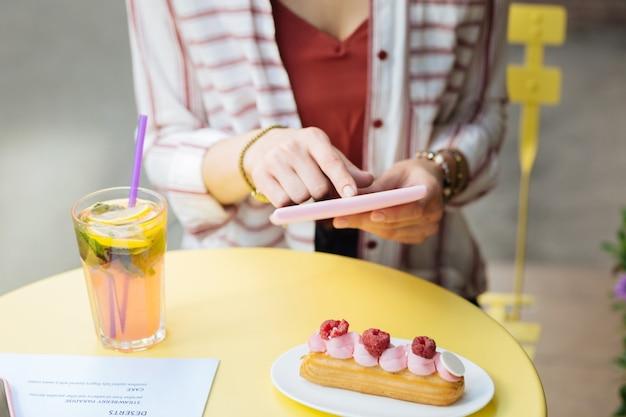Usando um tablet. jovem visitante de um café segurando um tablet moderno enquanto está sentado em um café de rua com uma sobremesa saborosa na frente dela