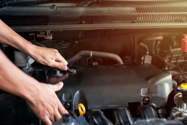 Usando uma chave para afrouxar os parafusos do compartimento do motor