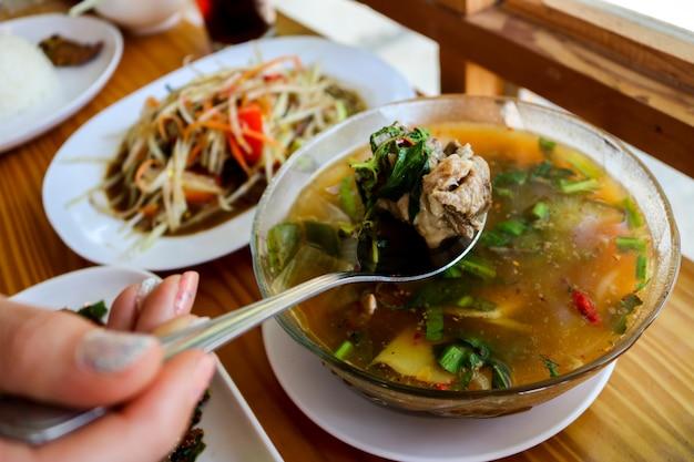 Usando uma colher, alimente a sopa de costela de porco em um restaurante e tenha um fundo desfocado.