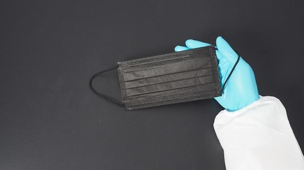Use à mão conjunto de epi e luvas e segurando máscara facial preta. coloque um fundo preto.