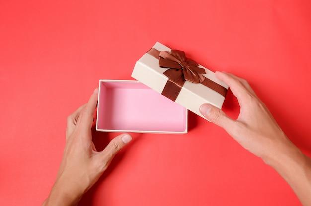 Use a mão para abrir a caixa de presente em um fundo vermelho.