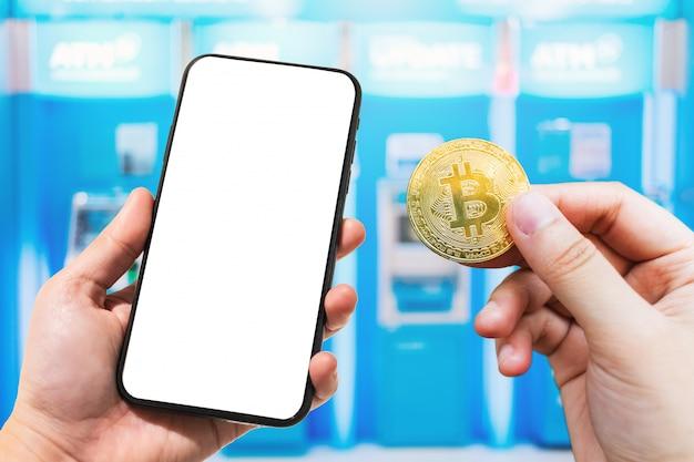 Use a mão segurando o smartphone e moeda de bitcoin