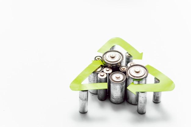 Use aa e descarte adequadamente as baterias que são tóxicas para o meio ambiente e o solo contra um fundo verde