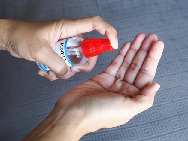 Use desinfetante com álcool em frasco de spray para limpar os germes de proteção das mãos coronavírus ou covid-19.
