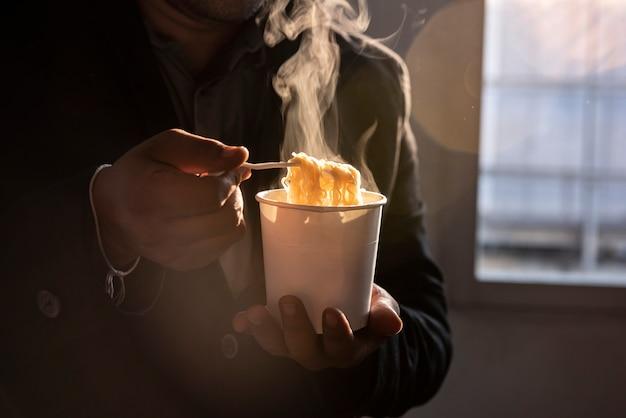 Use pauzinhos para lidar com macarrão. em uma panela com fumaça em um fogão asiático