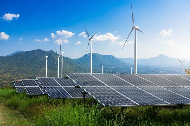 Usina de energia solar de módulos fotovoltaicos com turbinas eólicas contra paisagem de montanhas contra o céu azul com nuvens, conceito de energia alternativa, energia limpa, energia verde.