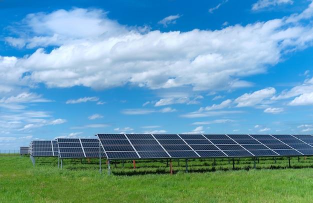 Usina de energia solar, painéis solares azuis em campo de grama verde sob um céu azul com nuvens