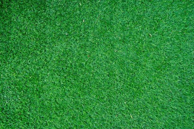 Uso artificial da grama da decoração verde para o fundo do esporte.