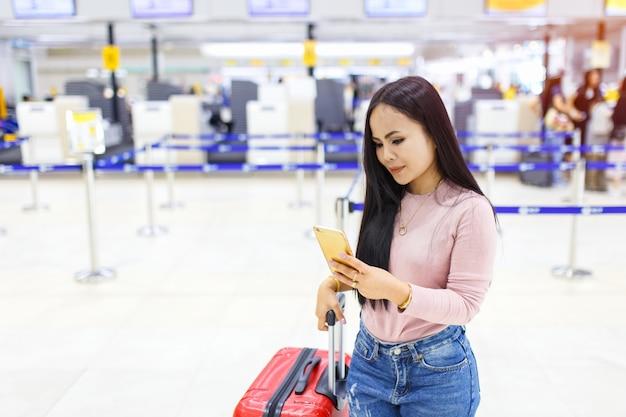 Uso asiático da mulher do telefone celular na frente da verificação contrária na linha aérea no aeroporto internacional.