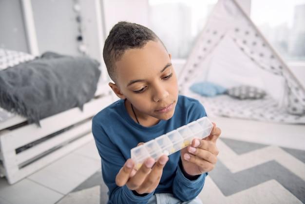 Uso correto. um lindo garoto afro-americano segurando um recipiente para drogas enquanto lê