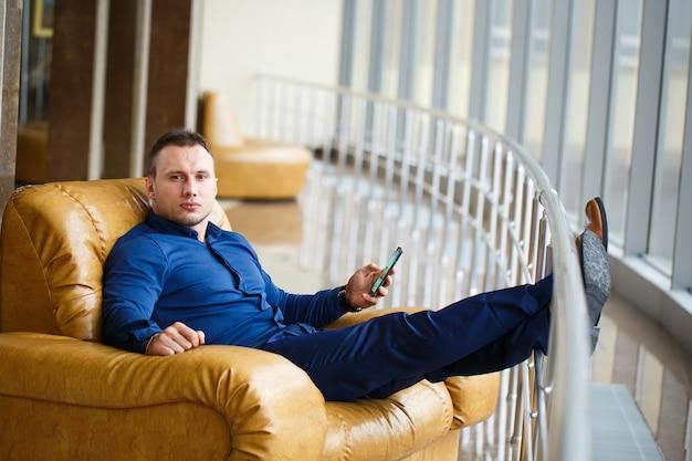 Uso de empresário de telefone celular e sentado na cadeira.
