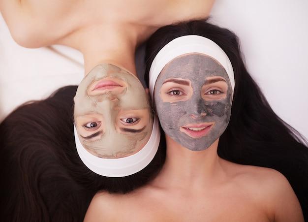 Uso de uma máscara facial para o rosto duas jovens mulheres em um salão de beleza