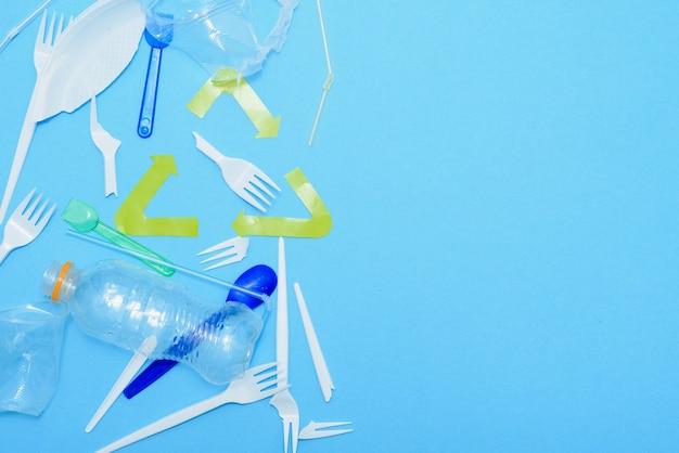 Uso único, talheres descartáveis e sinal de reciclagem no fundo. colheres, garfos