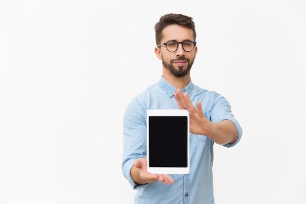 Usuário de tablet satisfeito positivo, mostrando a tela em branco