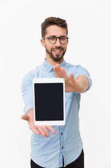 Usuário de tablet sorridente positivo, mostrando a tela em branco