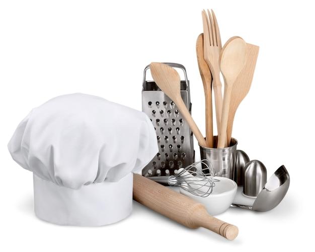 Utensílio de cozinha com chapéu de cozinheiro isolado no branco