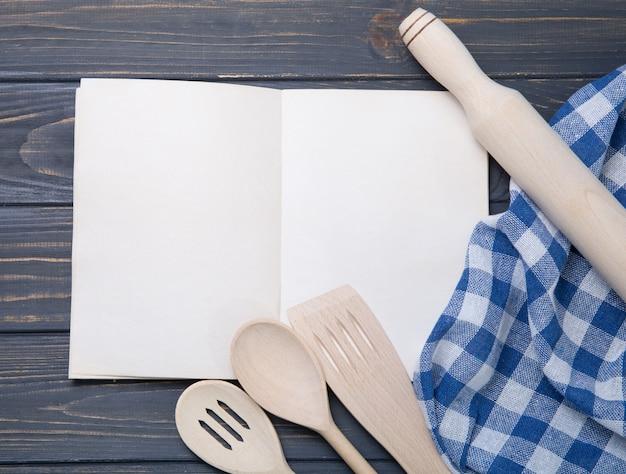 Utensílio de cozinha e o bloco de notas sobre fundo de mesa de madeira