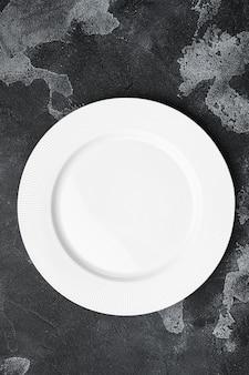 Utensílio vazio de prato branco definido com espaço de cópia para texto ou comida com espaço de cópia para texto ou comida, vista de cima plana lay, em fundo de mesa de pedra escura preta