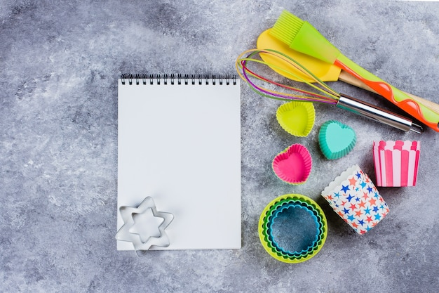 Utensílios da cozinha do arco-íris e caderno vazio (livro da receita) no fundo concreto cinzento da tabela.