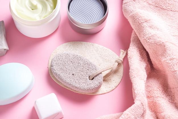 Utensílios de banho, toalha, pedra-pomes, creme e sabonete na mesa do banheiro