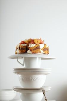 Utensílios de chá vintage brancos e colher de sobremesa de prata com um bolo de casamento não tradicional com chocolate, creme e frutas por cima