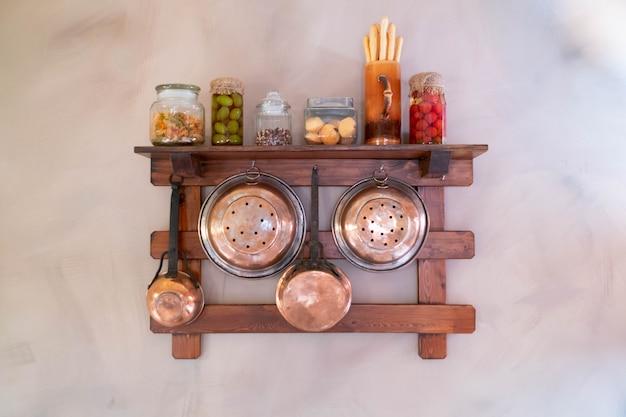Utensílios de cobre pendurado na prateleira: coador, dipper, frigideira, frascos, placa de corte.