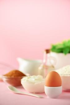 Utensílios de cozimento brancos no fundo cor-de-rosa. ingredientes alimentares. macro de ovo. cozinhar bolos e assar pão conceito. copie o espaço.