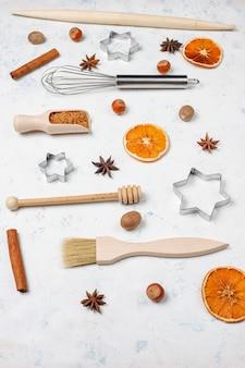 Utensílios de cozimento de cozinha com temperos para biscoitos e cortadores de biscoito na superfície da luz