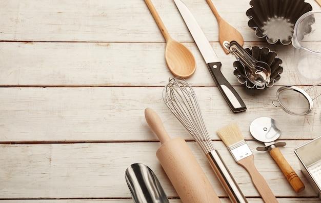 Utensílios de cozimento de cozinha contra mesa branca