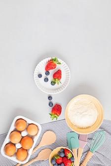 Utensílios de cozimento e ingredientes de cozinha para tortas, biscoitos, massa e pastelaria. postura plana com ovos, farinha, frutas.