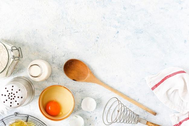 Utensílios de cozimento e ingredientes em um fundo branco