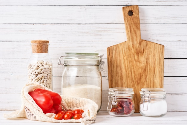 Utensílios de cozinha com tábua e recipientes de vidro reutilizáveis com ingredientes alimentares. zero conceito de resíduos