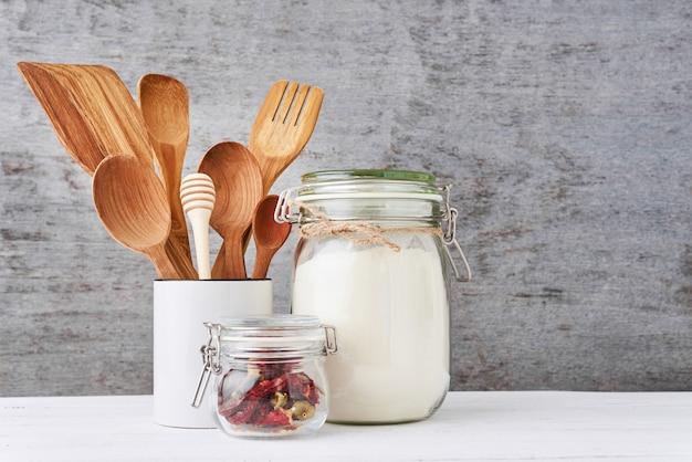 Utensílios de cozinha com talheres de madeira em copo cerâmico em uma mesa branca