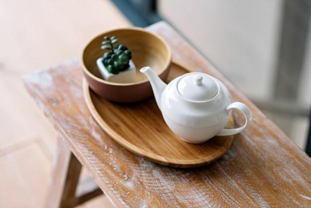 Utensílios de cozinha, como chaleira, cafeteira, em uma bandeja de madeira. café da manhã cedo. foco seletivo suave.