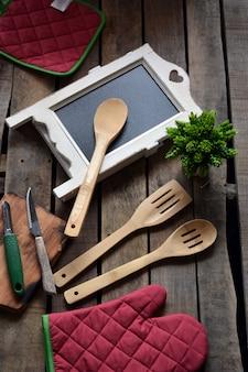 Utensílios de cozinha, como luvas de forno, colheres em madeira e ardósia para anotar o menu