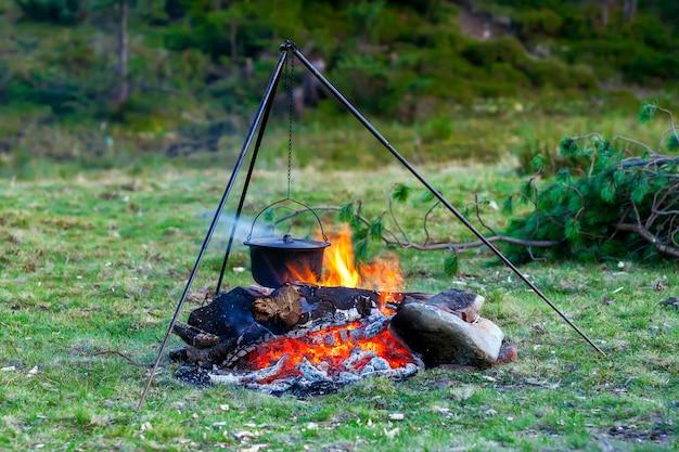 Utensílios de cozinha de acampamento - panela no fogo em um acampamento ao ar livre