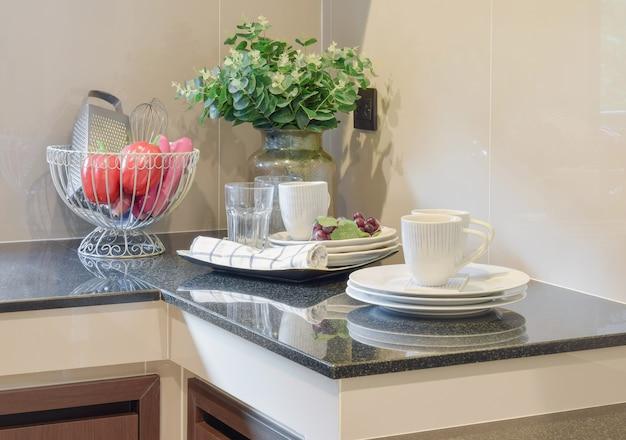 Utensílios de cozinha de cerâmica moderna e utensílios na bancada de granito preto