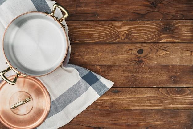 Utensílios de cozinha de cobre brilhante limpo na placa de madeira