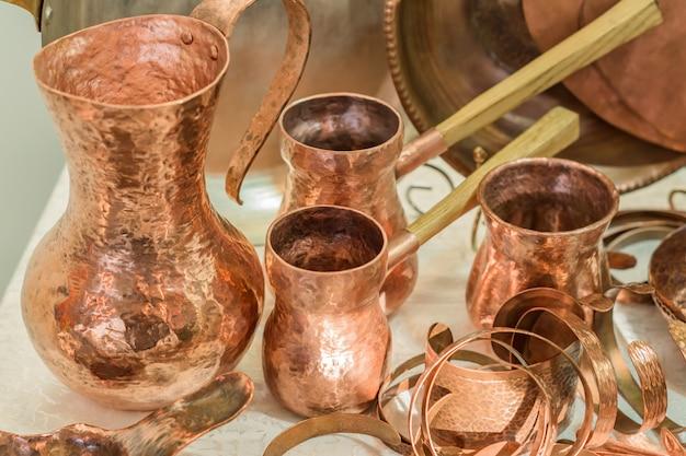 Utensílios de cozinha de cobre vintage - bules e jarros de café turco exibidos no mercado de pulgas